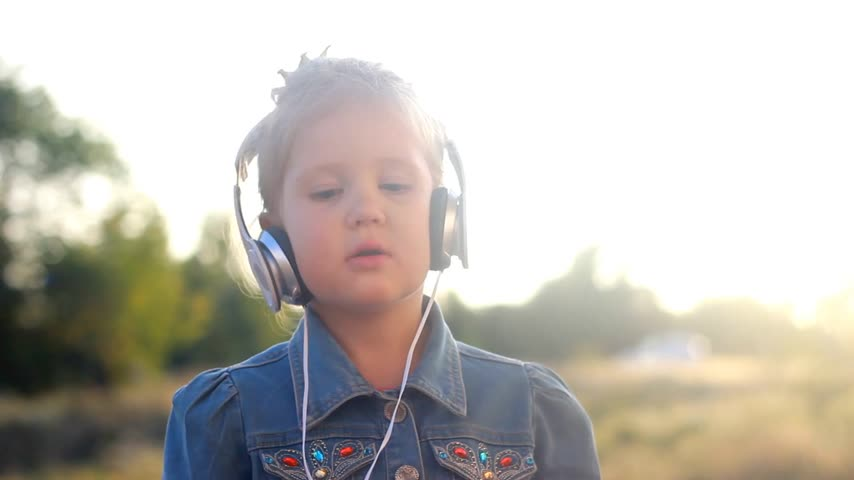 rhythmic : Child girl in headphones listens to music and rhythm. Portrait closeup baby at sunset on a summer day