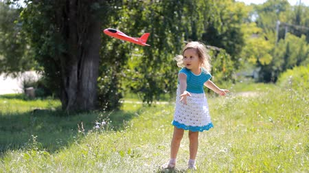 desejo : Child girl in the park is playing with an airplane. Baby starts the plane