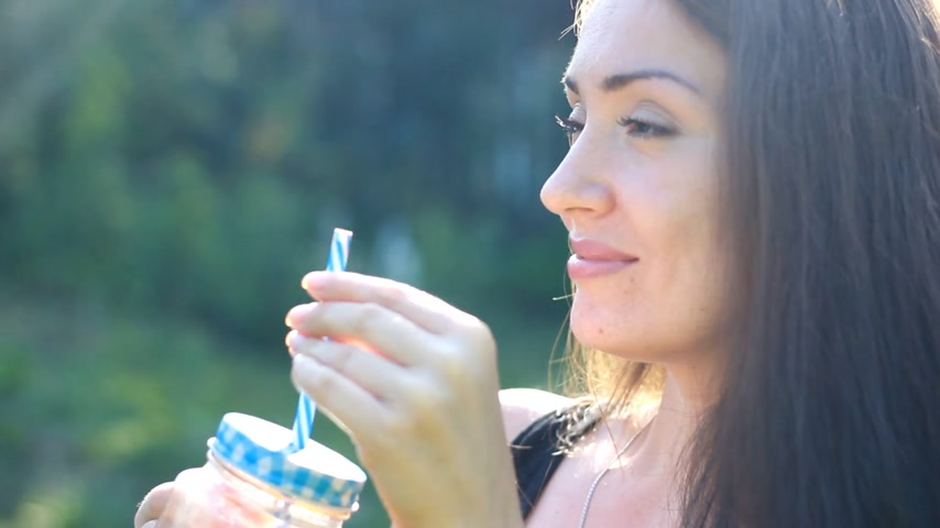 вегетарианство : Woman drinks smoothies or orange fresh outdoors.