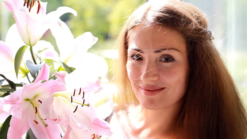 kacérkodás : Young beautiful woman with lily. Cute girl smells the scent of flowers. Stock mozgókép