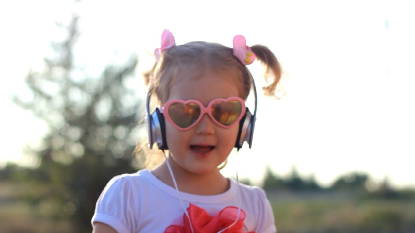 рэп : Funny child in headphones listens to music, sings and dances. Lovely girl in sunglasses at sunset on a summer day. Стоковые видеозаписи