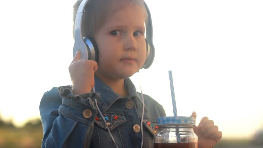 рэп : Child girl in headphones listens to music and drinking cocktail, juice, smoothies. Стоковые видеозаписи