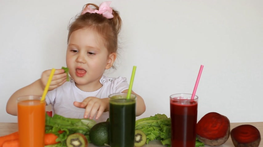 家庭 : Cute baby eats green leaves of lettuce. Child girl drinking vegetable smoothies - Carrot, beet and green. 影像素材