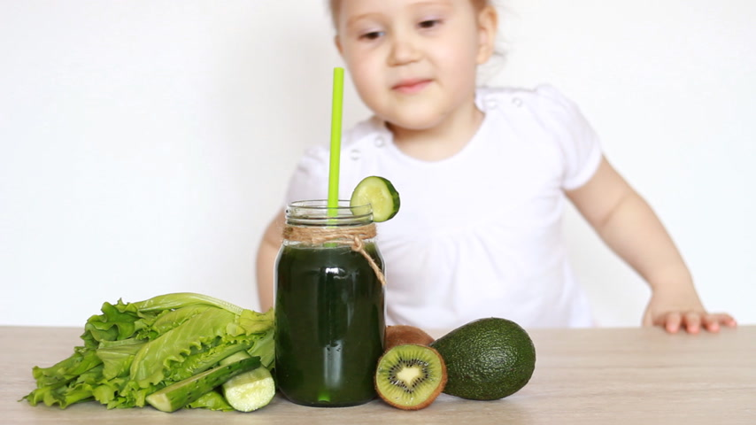 suco : Child girl shows emotions that she does not like vegetarian food and vegetable green smoothies.