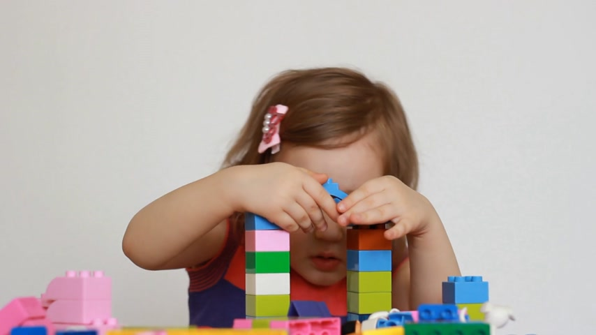 interessado : Child girl is busy building a constructor. Baby playing a game Vídeos