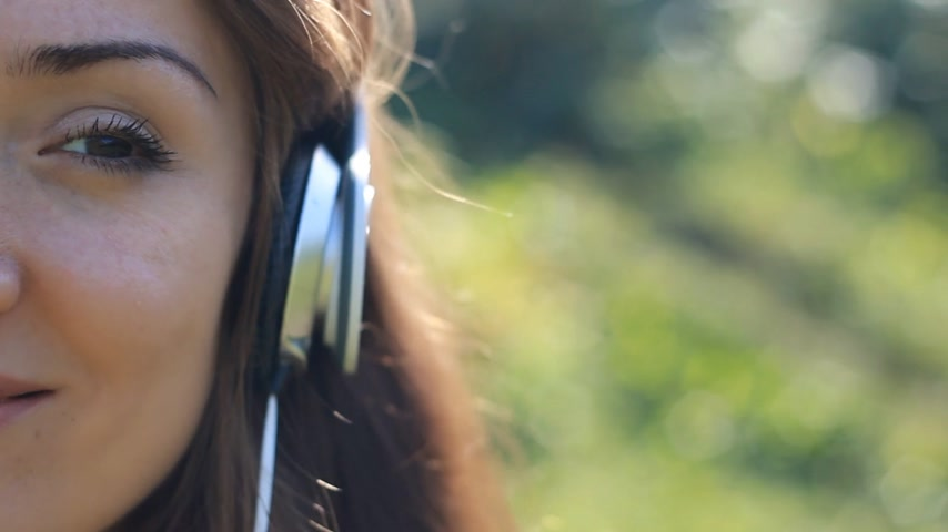 rhythmic : Young woman in headphones listens to music. Portrait closeup