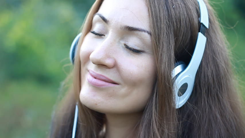 dal : Woman listening to music in headphones on the outdoor. Portrait of a beautiful close-up girl