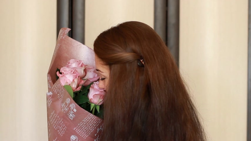 kacérkodás : Young woman with a bouquet of roses smiling and sniffing the fragrance.