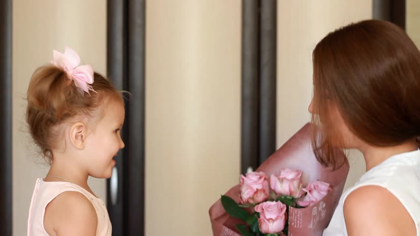 smelling : Woman and her child girl with a bouquet of roses smiling and sniffing the fragrance. Stock Footage