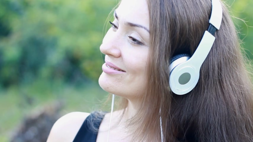 rhythmic : Woman in headphones listening to music. Portrait beautiful girl. Face closeup Stock Footage