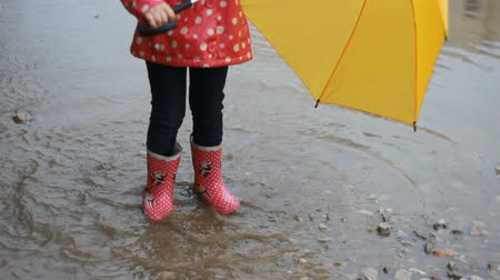 raincoat : Funny child girl jumping and playing in puddles in rainy weather under an umbrella