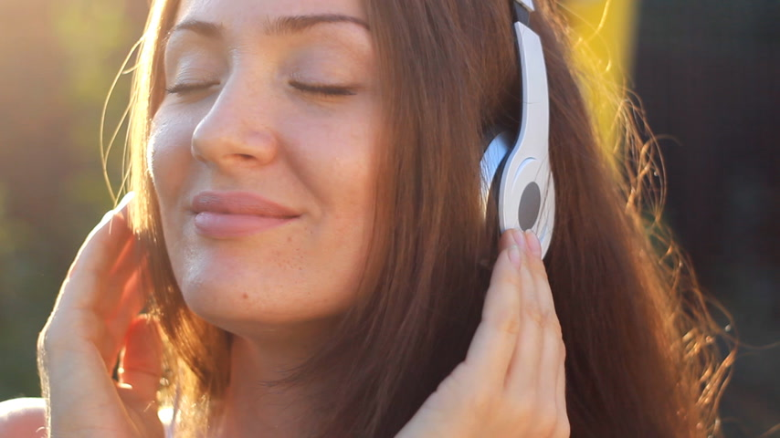 ритмичный : Woman in headphones listening to music at sunset with sun rays on the outdoor Portrait of a beautiful closeup girl.