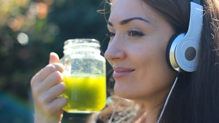 üretim : Woman drinking green smoothies and listening to music with headphones close-up portrait