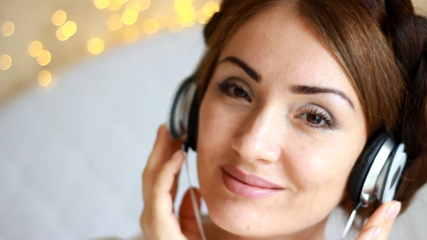 рэп : Beautiful woman in headphones listening to a musical song on light background