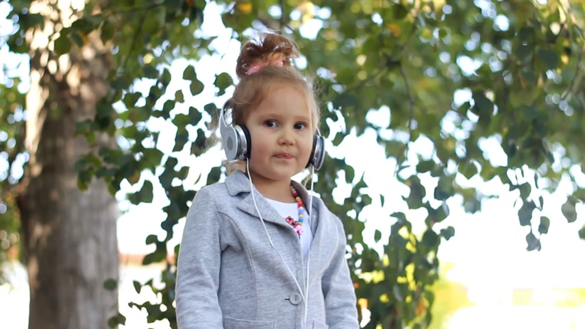 рэп : Cute child girl in headphones listening to music and singing a song in a park with birches Стоковые видеозаписи