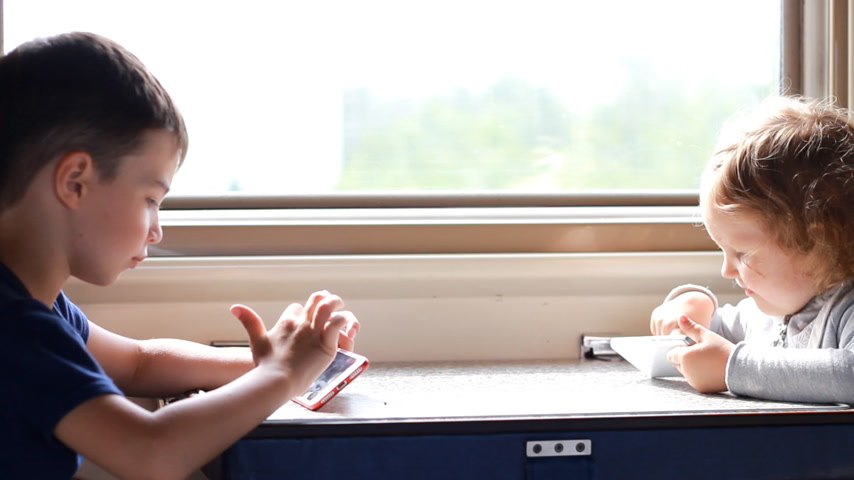 visto : Children girl and boy play in the game with smartphone in train.