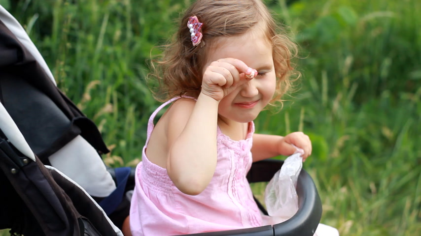 wozek dzieciecy : Child girl sitting in a baby stroller and eating cookies Wideo