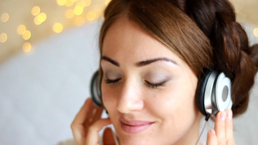 рэп : Woman in headphones listening to a music song with eyes closed.