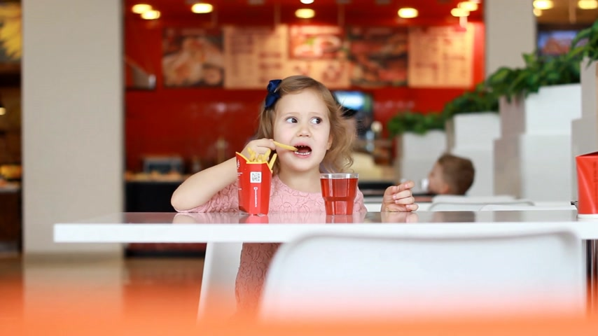 жевать : Child girl eating fast food french fries and drinking juice in a cafe.