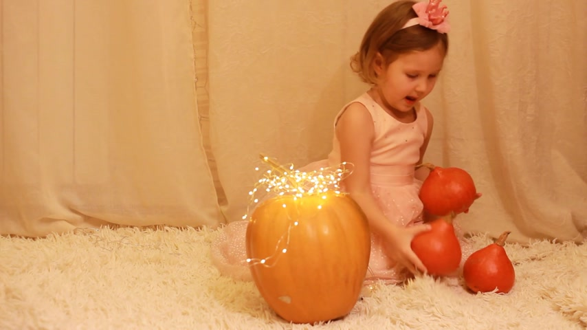 クラウン : Child girl princess with a crown on her head, in the dress playing with pumpkins.