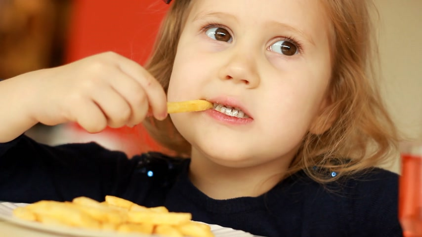 nibble : Child girl eating fast food french fries in a cafe. Portrait closeup Stock Footage