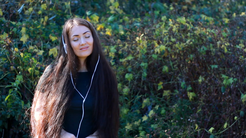 chant : Woman in headphones smiling and enjoying a song with her eyes closed outdoor.