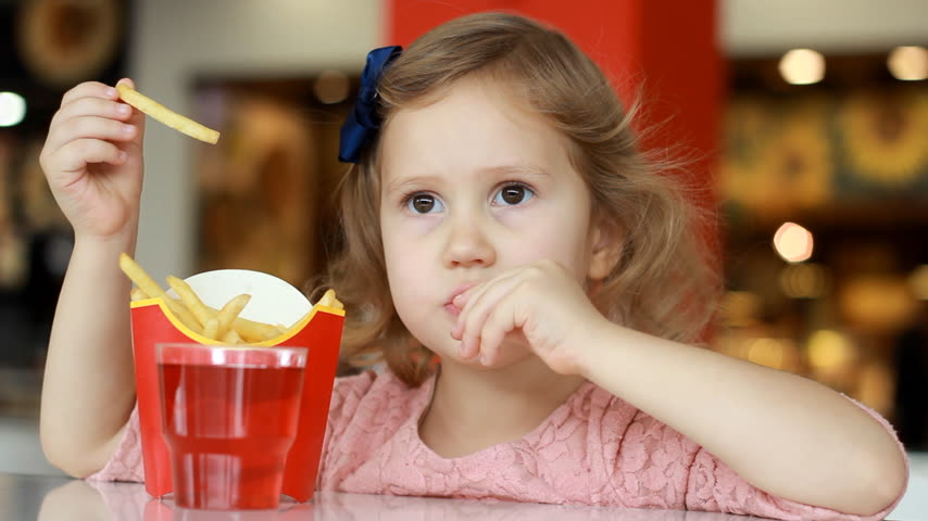 pepite : Baby girl eating fast food french fries in a cafe. Portrait closeup. Filmati Stock