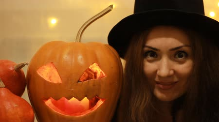 witch hat : Halloween. Woman in the black hat with pumpkins. Portrait close up