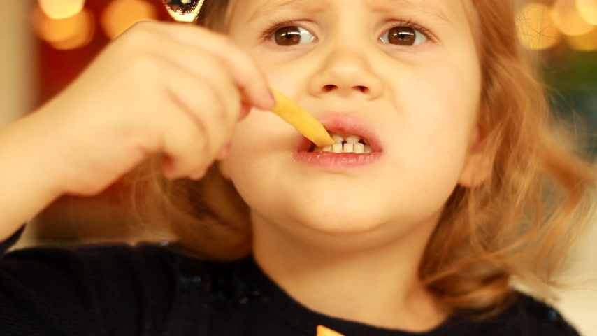 nibble : Baby girl eating fast food french fries in a cafe. Portrait closeup. Stock Footage