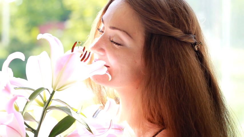 kacérkodás : Beautiful woman closeup smiling and snifing flowers lily