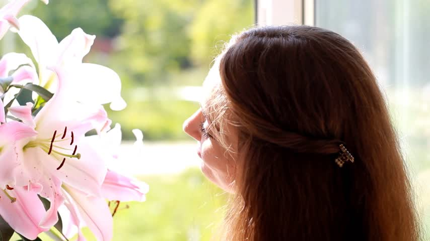 kacérkodás : Beautiful woman closeup with flower lily. Advertisement. Advertising. Smile face. Flirt.