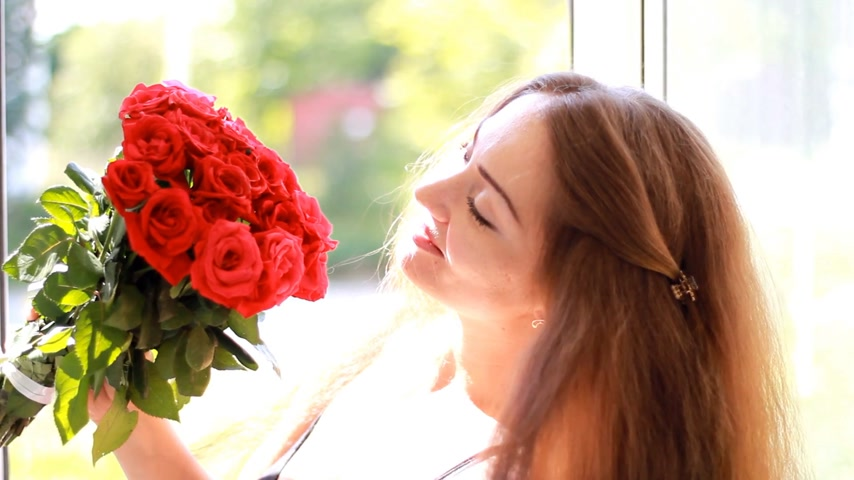 kacérkodás : Beautiful woman closeup smiling and sniffing aroma of flowers of red roses. Stock mozgókép
