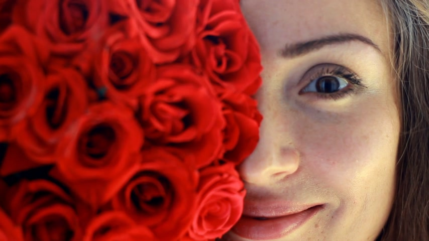 cheirando : Beautiful woman closeup smiling and sniffing aroma of flowers of red roses