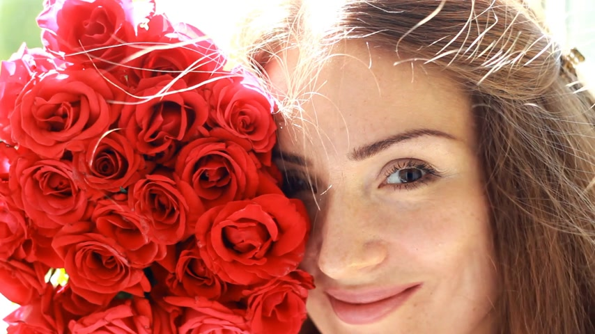 kacérkodás : Beautiful woman closeup smiling and sniffing aroma of flowers of red roses. Wind in the hair girl. Stock mozgókép