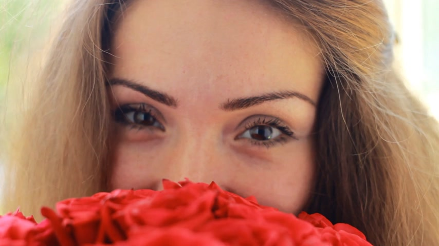 kacérkodás : Beautiful woman closeup with a bouquet of flowers of red roses.