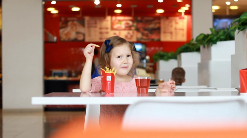 pepites : Child girl eating fast food french fries and drinking juice in a cafe.