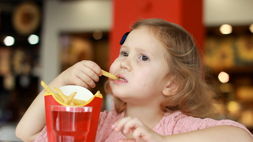 nibble : Child girl eating fast food french fries and drinking juice in a cafe.