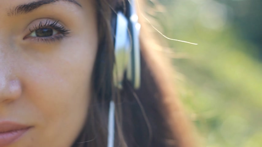 chant : Woman closeup in headphones listening music. Sad melody and sadness in the eyes