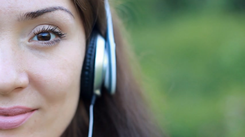 chant : Beautiful woman in headphones listening to music. Half face closeup. Mood, pleasure, relaxation, relax.