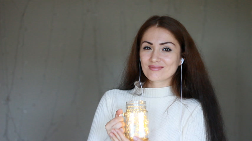 ритмичный : Beautiful woman close up puts on headphones and listens to music on the background of magical lights
