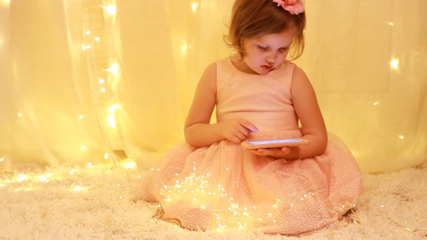 néz : Child playing a game on a mobile phone. Baby is watching video on smartphone.