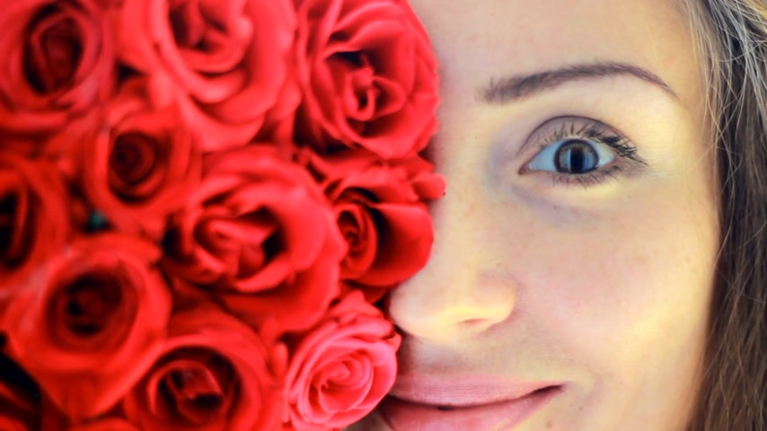 kacérkodás : Face closeup of a beautiful young woman with red roses.