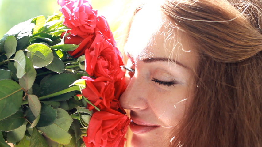 cheirando : Beautiful woman closeup smiling and sniffing aroma of flowers of red roses. Wind in the hair girl