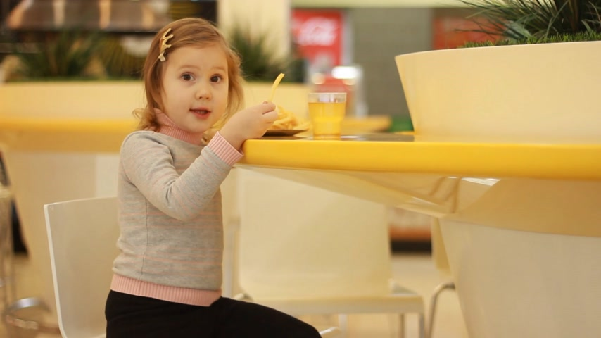 pepite : Child girl eating fast food french fries in a cafe.