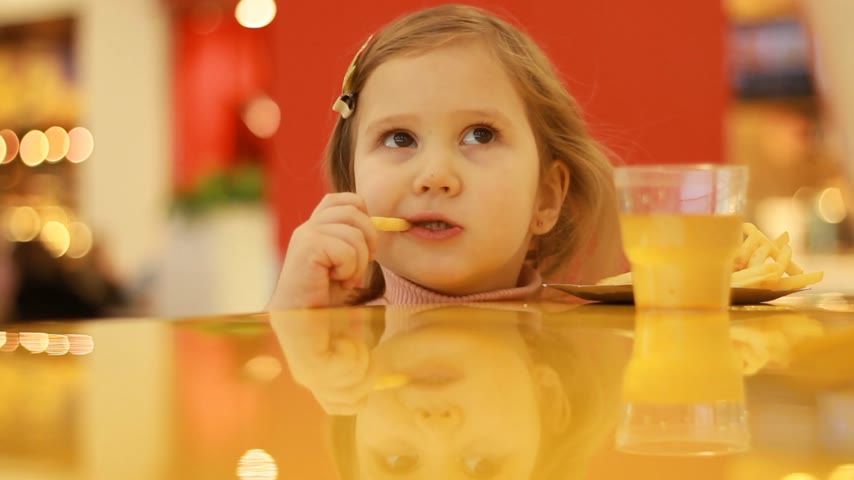 pepite : Child girl eating fast food french fries in a cafe. Portrait closeup. Filmati Stock