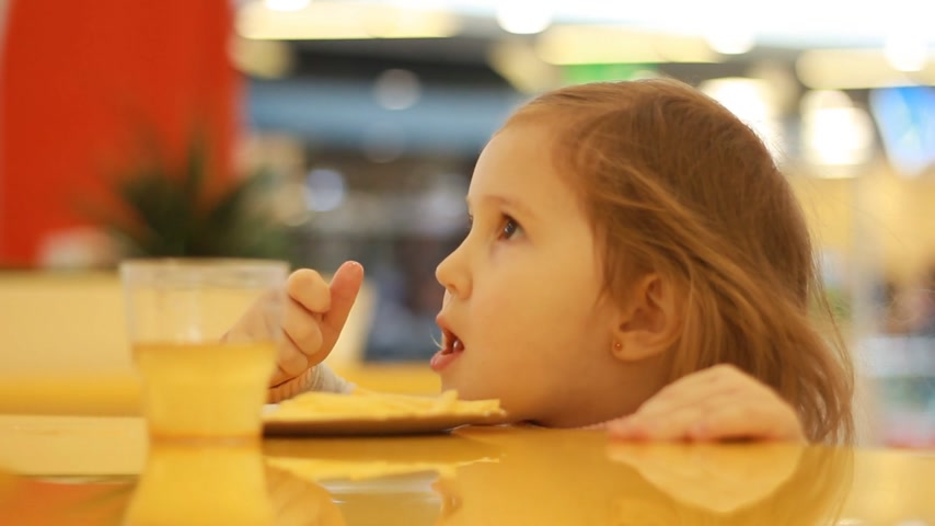 nibble : Child girl eating fast food french fries in a cafe. Portrait closeup. Stock Footage