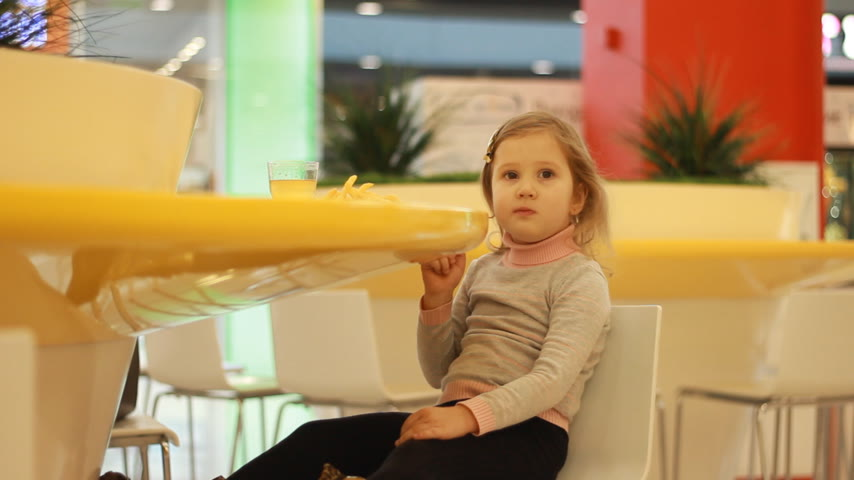 pepite : Baby girl eating fast food french fries in a cafe. Filmati Stock