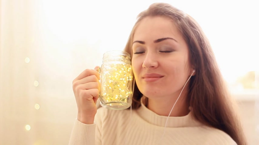 rapper : Woman in headphones listening to music, looking at the lights, closes her eyes and relaxes.