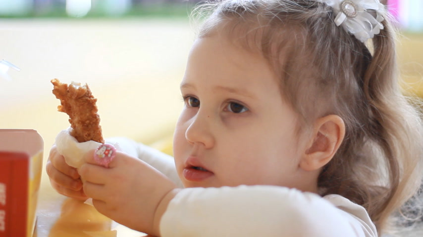 nibble : Child eating nuggets closeup. Portrait of a baby who eats fast food Stock Footage