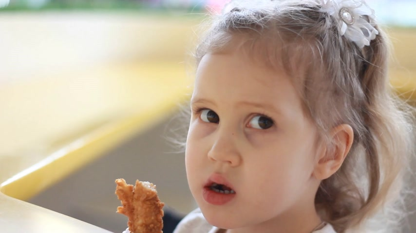 mastication : Child eating nuggets in the cafe. Portrait of a baby who eats fast food